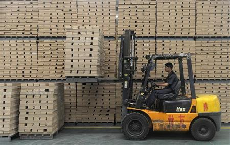 A worker operates a forklift to transport floor boards at a wood flooring factory in Huzhou